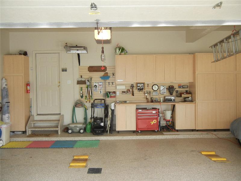 A dream HEATED 3 car garage with a finished floor, hot and cold water and great storage cabinets.